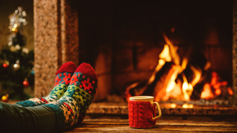46927057 - feet in woollen socks by the christmas fireplace. woman relaxes by warm fire with a cup of hot drink and warming up her feet in woollen socks. close up on feet. winter and christmas holidays concept.