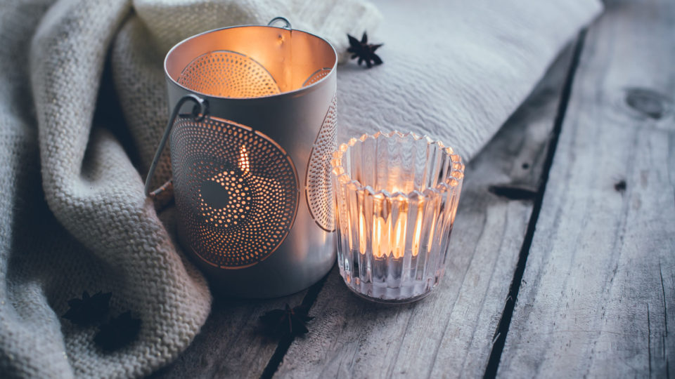 47713082 - cosy and soft winter background, knitted sweater and candles on an old vintage wooden board. christmas holidays at home.